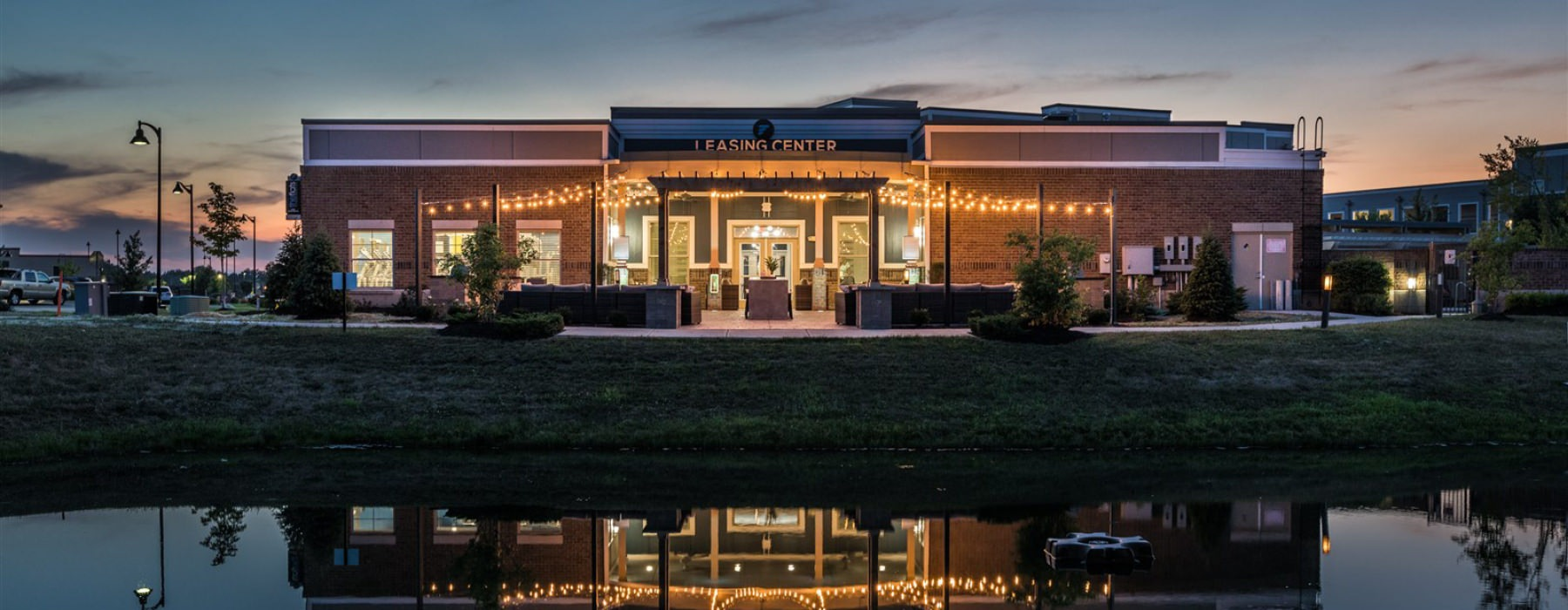 Night view of The Flats at Fishers Marketplace leasing office.